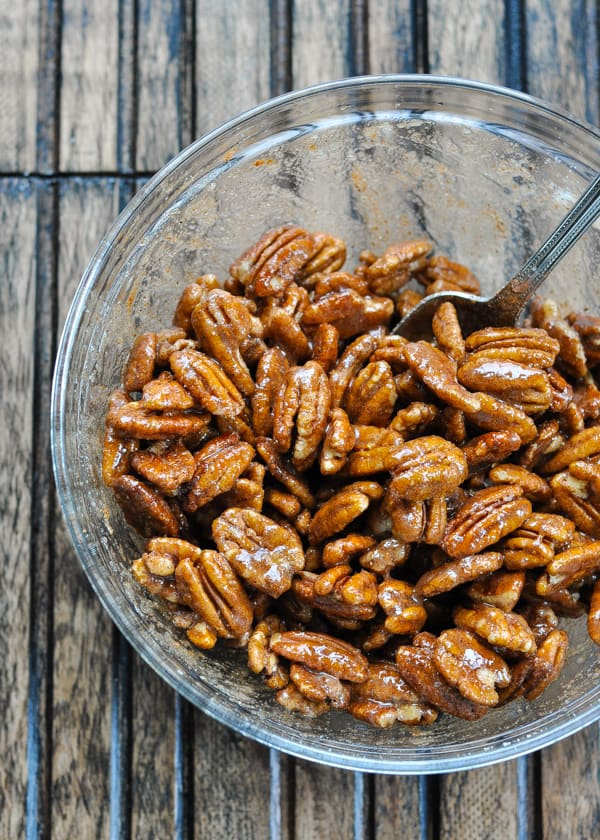 Candied pecans in a glass bowl before baking