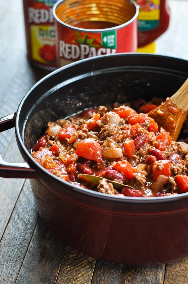 Stirring together chili con carne ingredients in pot with wooden spoon