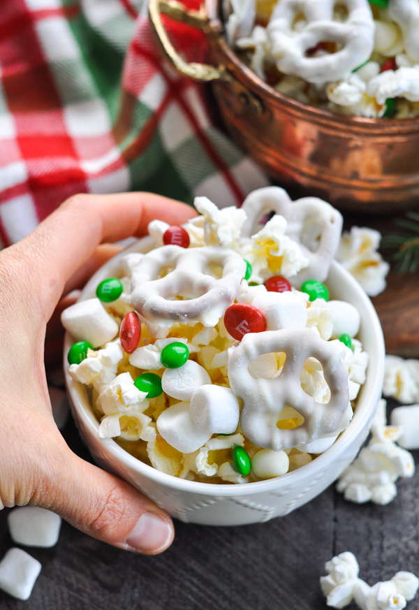 Hand holding small bowl of Christmas Snack Mix with M&M's