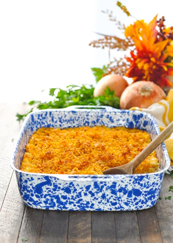 Front view of hash brown casserole in a blue and white baking dish with Corn Flakes on top