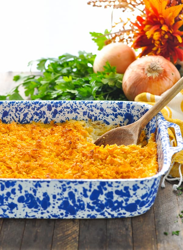 Easy Hash Brown Casserole in a blue and white baking dish with wooden spoon