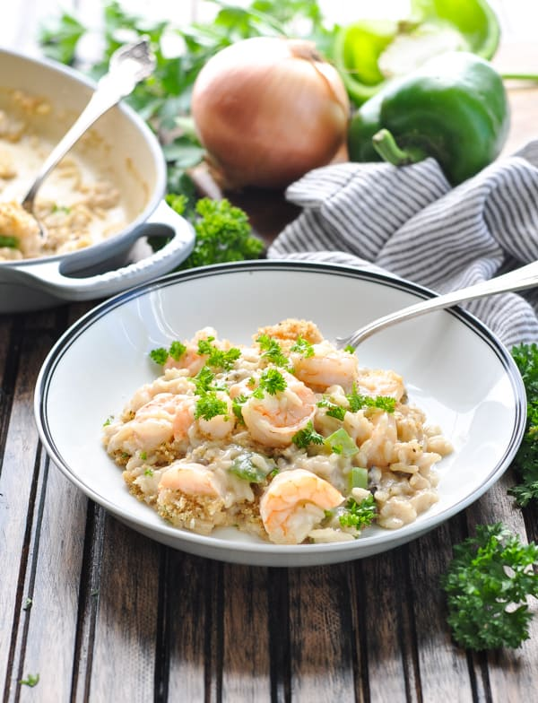 Bowl of creamy shrimp and rice casserole garnished with fresh parsley