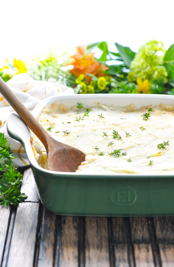 Turkey Shepherd's Pie in a green casserole dish with wooden spoon