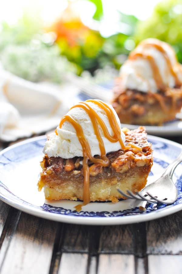 Pecan Pie Bar on a plate with vanilla ice cream and caramel sauce