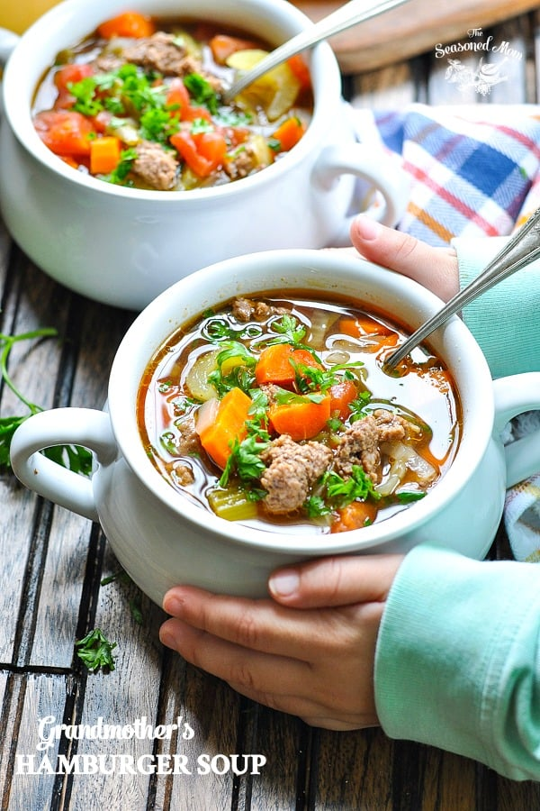 Child's hands holding a bowl of healthy and easy Hamburger Soup