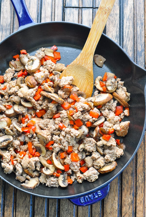 Cooked italian sausage in a skillet with mushrooms and red bell pepper