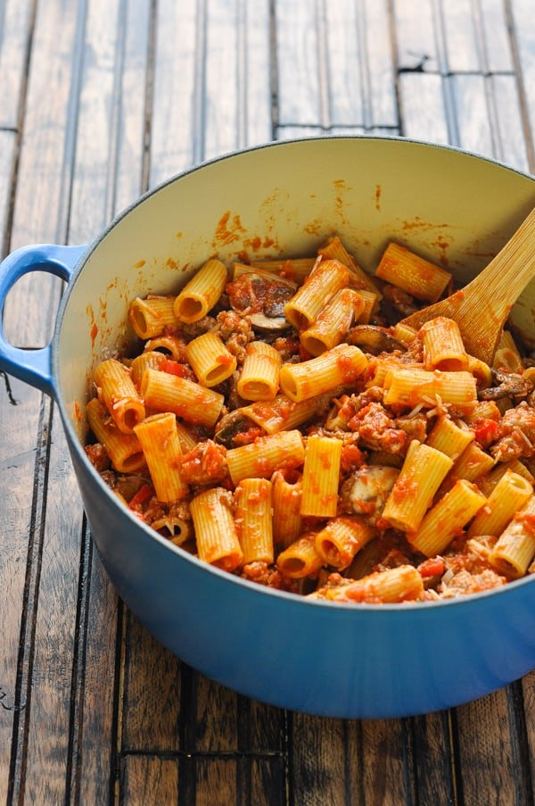 Italian sausage pasta in a blue pot with wooden spoon