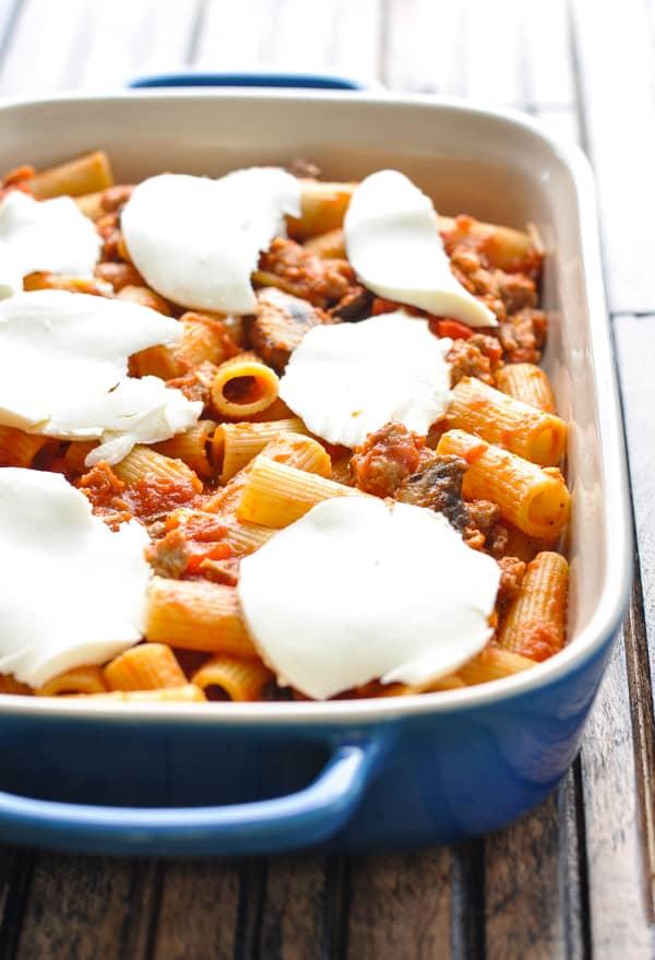 Layering Italian Pasta Sausage Bake in blue casserole dish