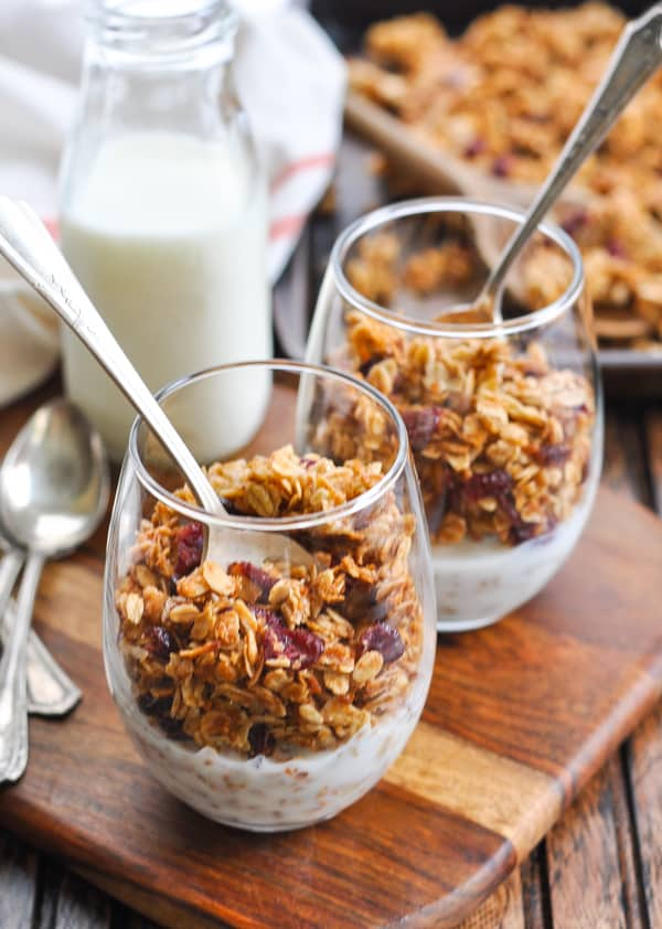 Homemade crunchy granola in glasses with milk
