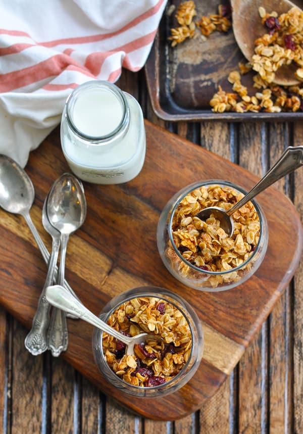 Overhead image of two glasses of granola with bottle of milk