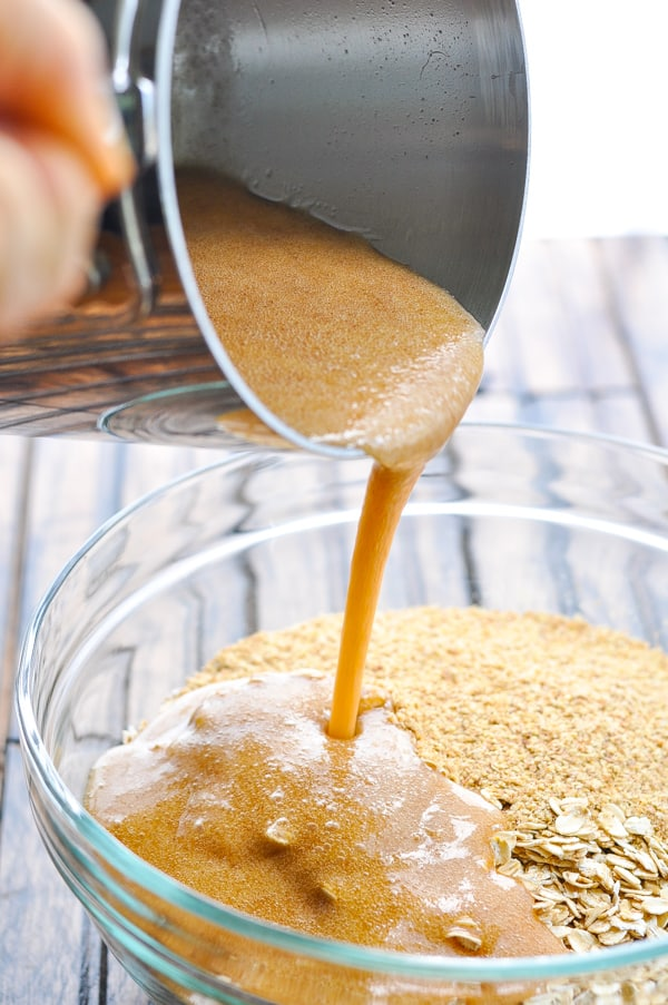 Pouring honey mixture over bowl of oats