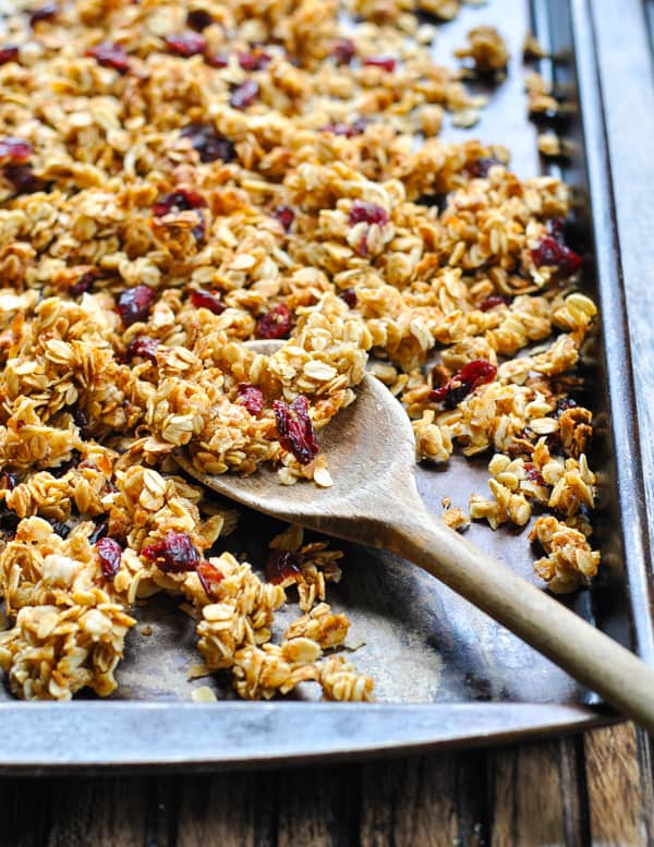 Crunchy granola clusters on baking sheet with wooden spoon