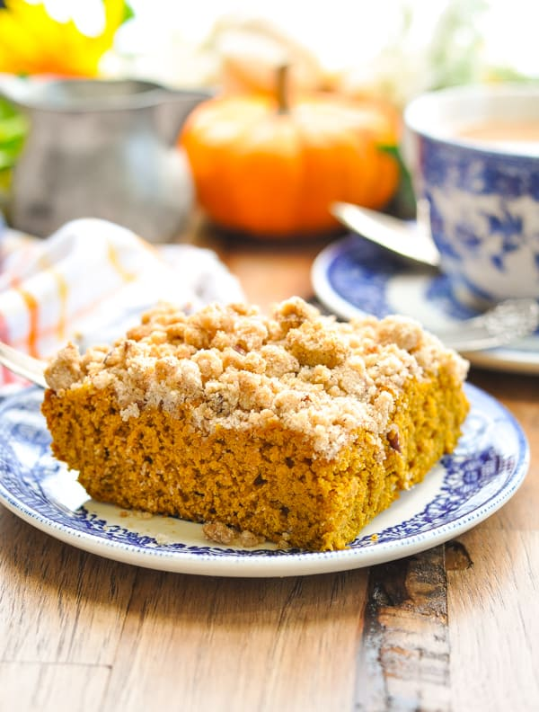 Slice of pumpkin coffee cake with pecan streusel on blue and white plate