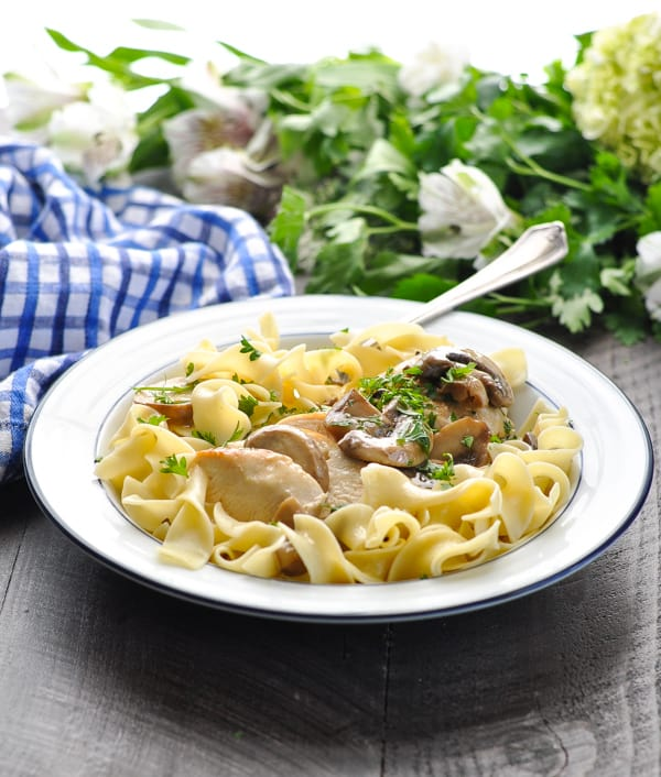Bowl of noodles with chicken and creamy mushroom sauce garnished with parsley