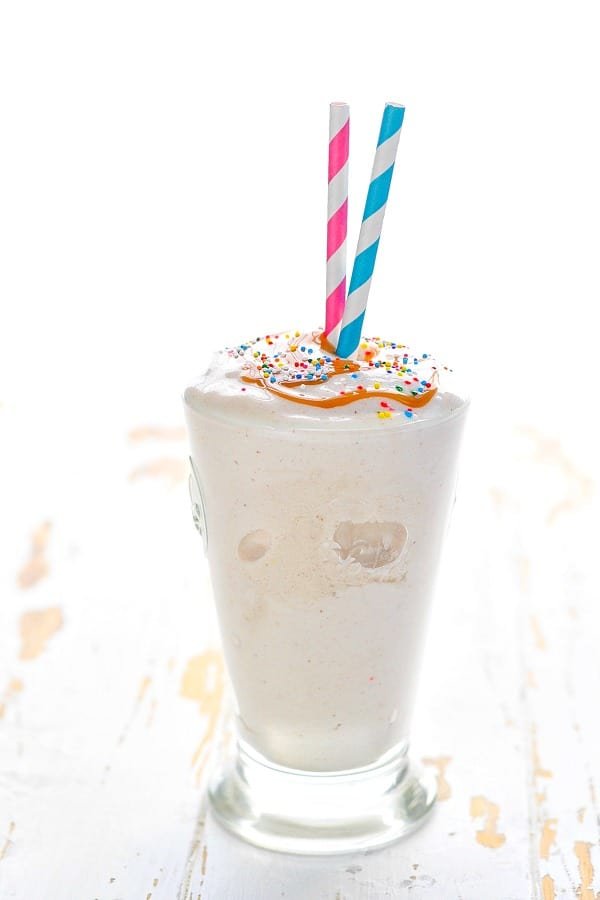 Glass of bananas foster protein smoothie with sprinkles and caramel sauce