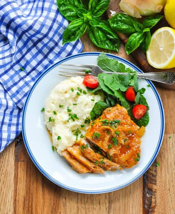 Overhead image of smothered pork chops on a blue and white plate with mashed potatoes