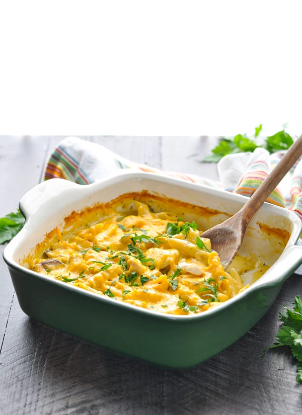 Chicken Penne Pasta recipe in a green baking dish with wooden spoon