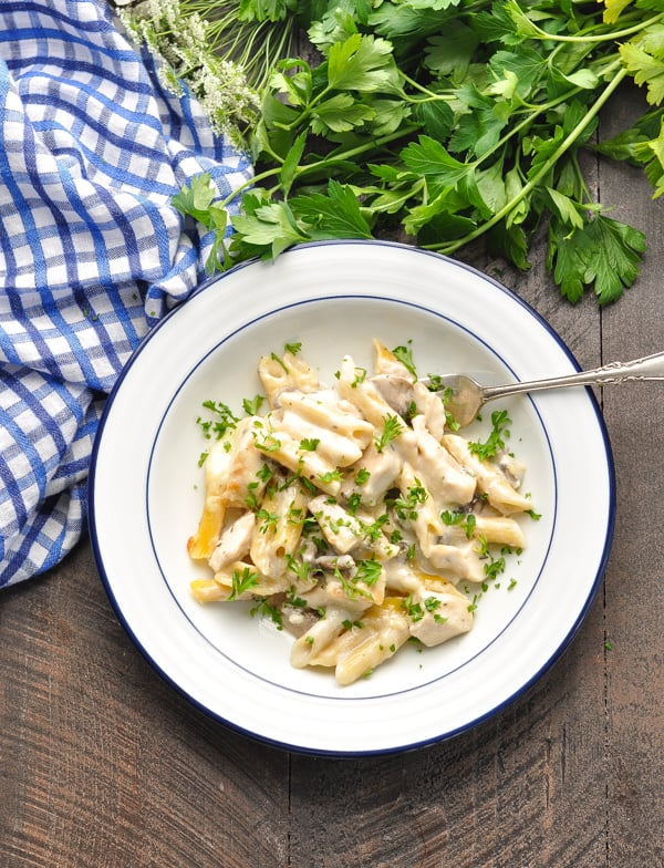 Overhead image of bowl of chicken and mushroom pasta bake with a fork