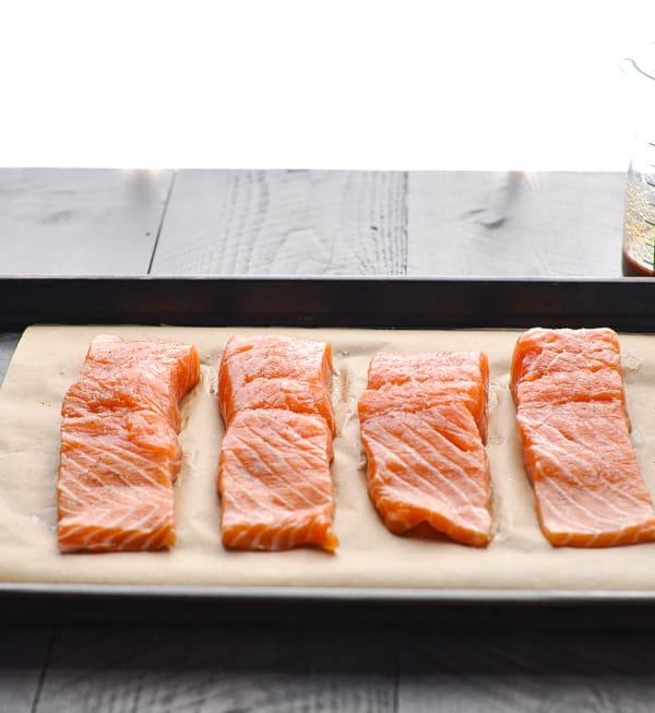 Raw salmon fillets on parchment lined baking sheet