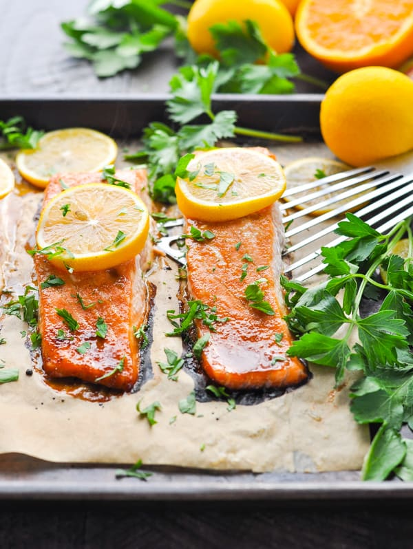 Oven baked glazed salmon on baking sheet garnished with lemon slices