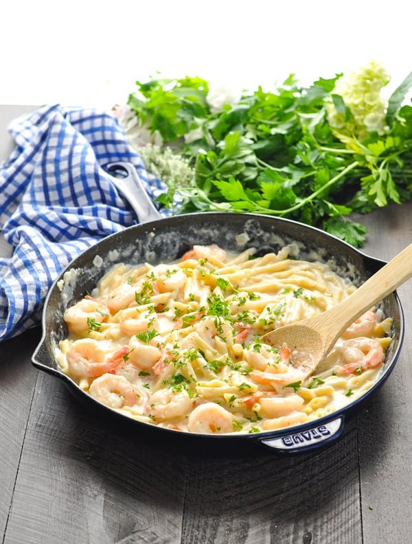 Healthy Shrimp Alfredo Pasta in a cast iron skillet garnished with parsley
