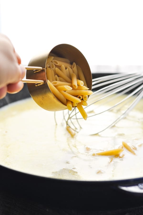 Adding penne pasta to alfredo sauce