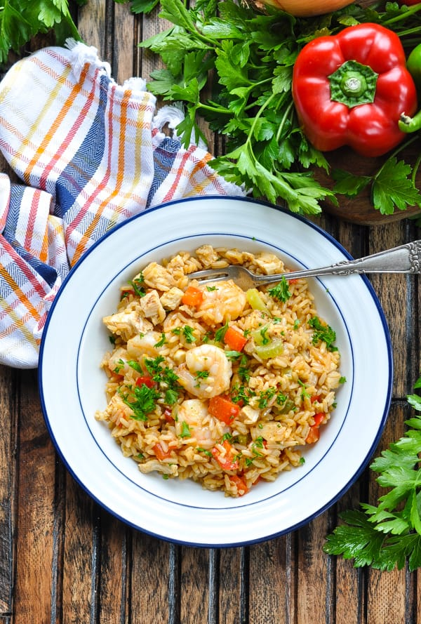 Overhead image of bowl of one pot turkey jambalaya with shrimp garnished with parsley and a fork