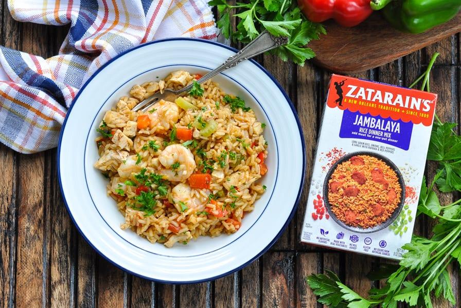 Horizontal overhead image of bowl of turkey jambalaya with shrimp and box of Zatarain's rice mix