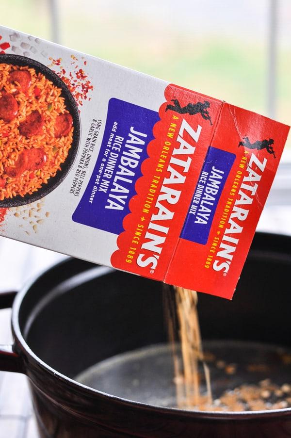 Pouring Zatarain's rice mix into pot