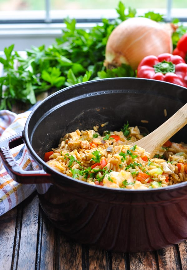 Pot of turkey jambalaya with shrimp and a wooden serving spoon