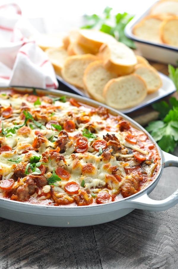 Casserole dish full of easy layered pizza dip recipe garnished with parsley
