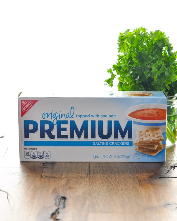 Box of saltine crackers and jar of fresh parsley for salmon patties recipe