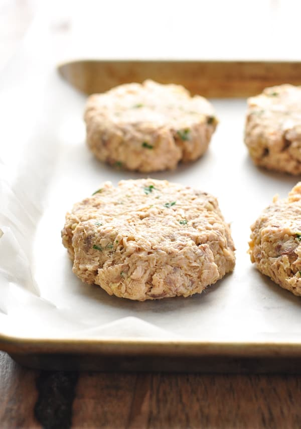 Raw salmon patties placed on a baking sheet lined with wax paper