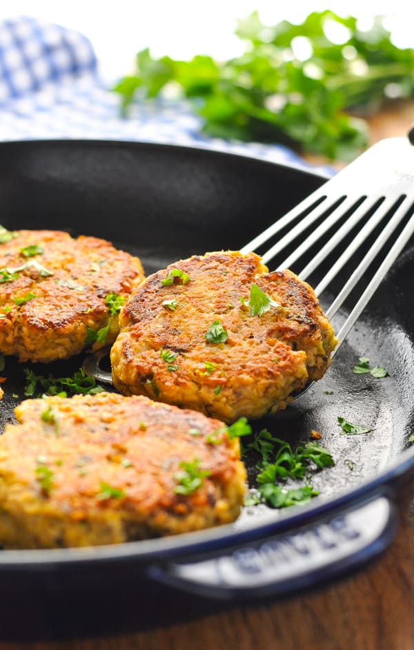 Salmon patties in a skillet on a spatula