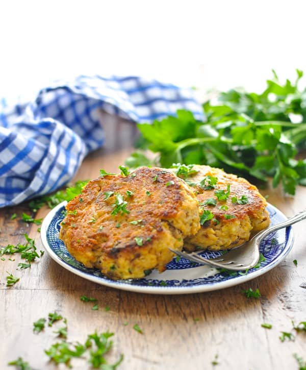 Two salmon patties on a blue and white plate garnished with parsley