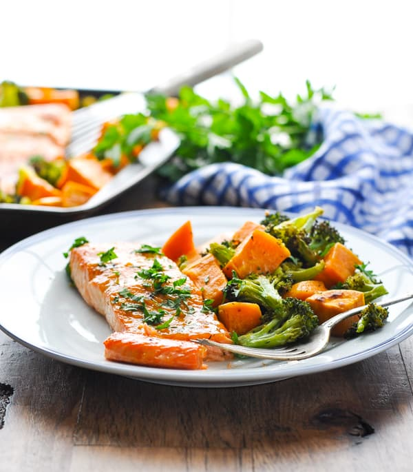 Broiled salmon fillet with sweet potatoes and broccoli on a blue and white plate
