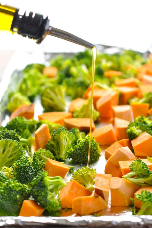 Drizzling olive oil over broccoli and sweet potatoes on a baking sheet