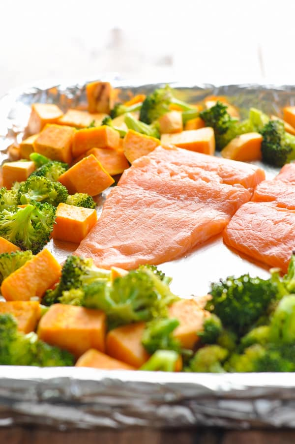 Raw salmon placed in the center of a baking sheet and surrounded by sweet potatoes and broccoli