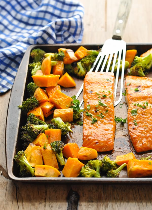 Broiled sheet pan dinner with salmon sweet potatoes and broccoli on a spatula