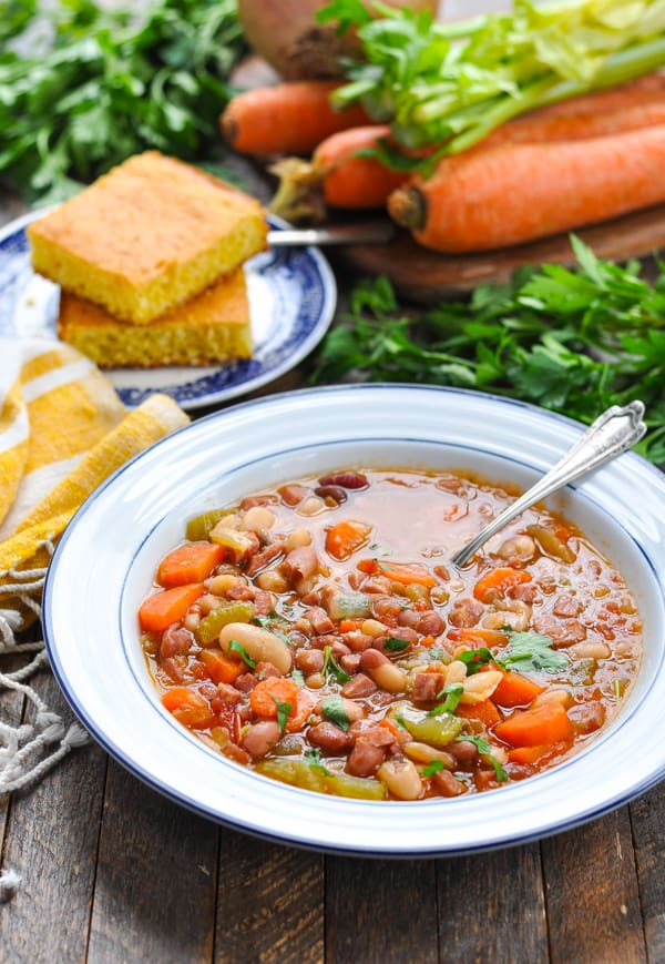 Bowl of healthy bean soup with cornbread and fresh vegetables in the background