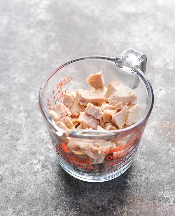 Diced rotisserie chicken breast in glass measuring cup