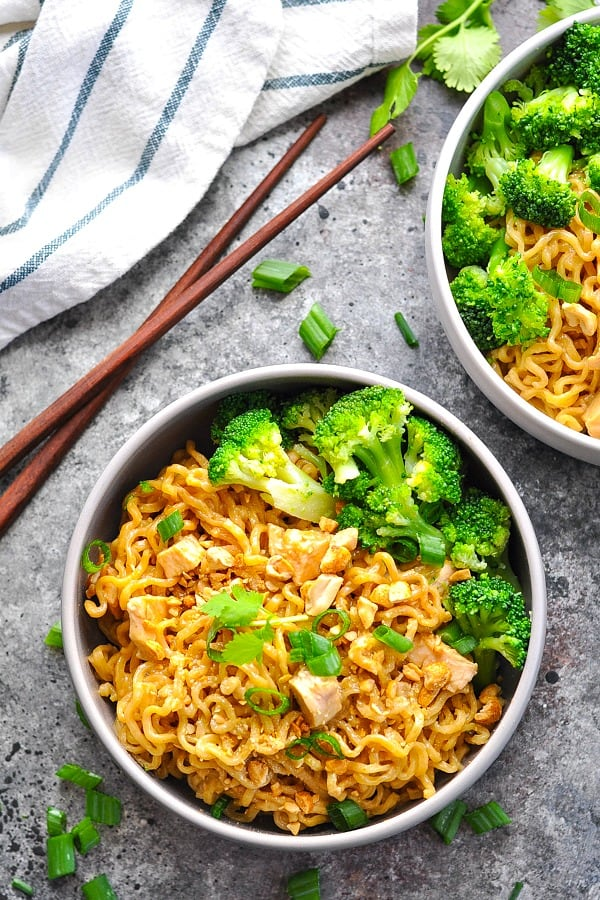 Overhead image of bowl of chicken ramen noodles in peanut sauce with steamed broccoli