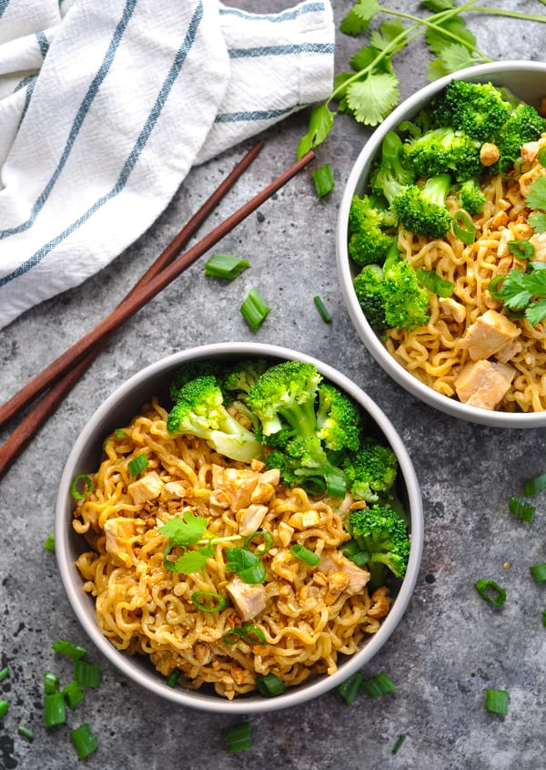 Overhead image of two bowls of Chicken Ramen in Peanut Sauce with chopsticks on table