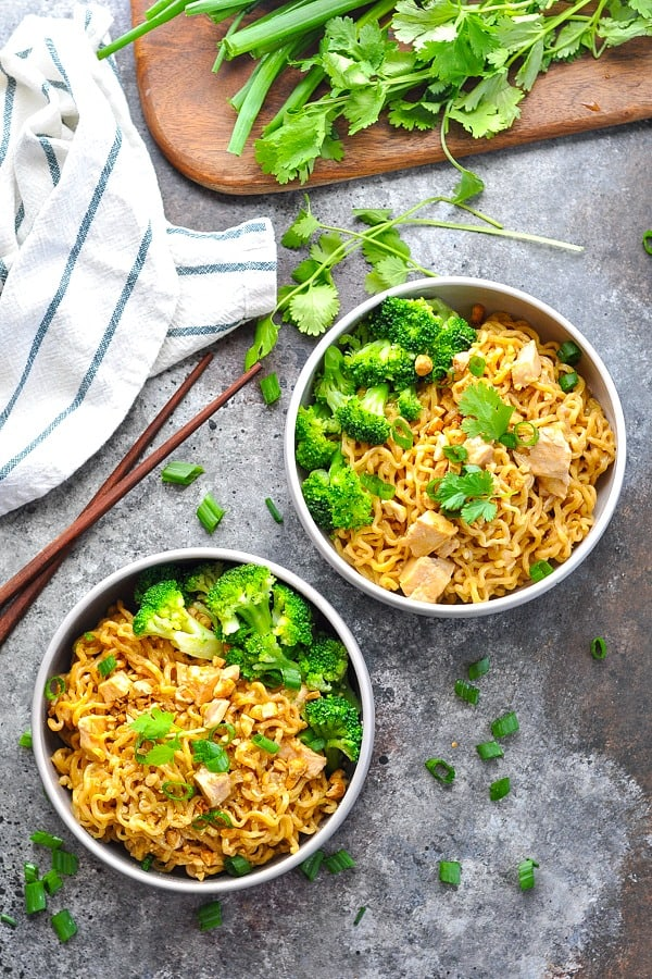 Long overhead image of two bowl of chicken ramen noodles in peanut sauce with steamed broccoli