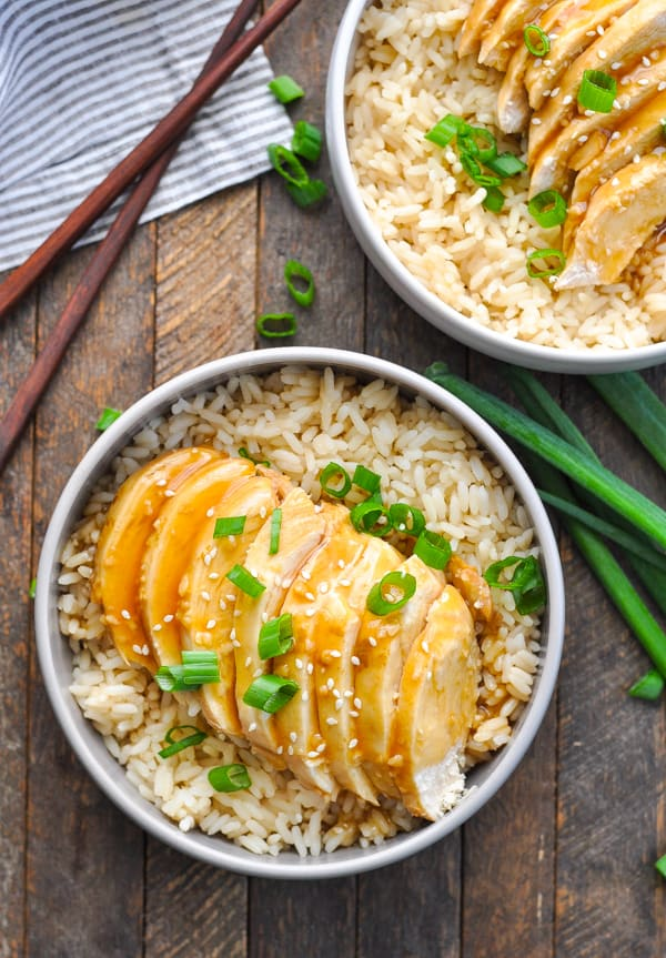 Close overhead shot of sliced teriyaki chicken in a bowl of rice garnished with green onion