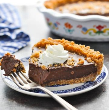Slice of Chocolate Pudding Pie with Graham Cracker Crust on a plate with a bite taken out