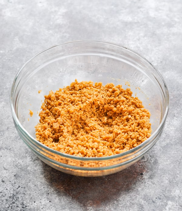Buttered graham cracker crumbs in glass mixing bowl