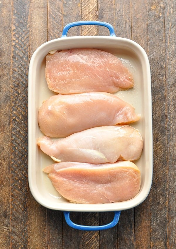 Raw chicken breasts in baking dish