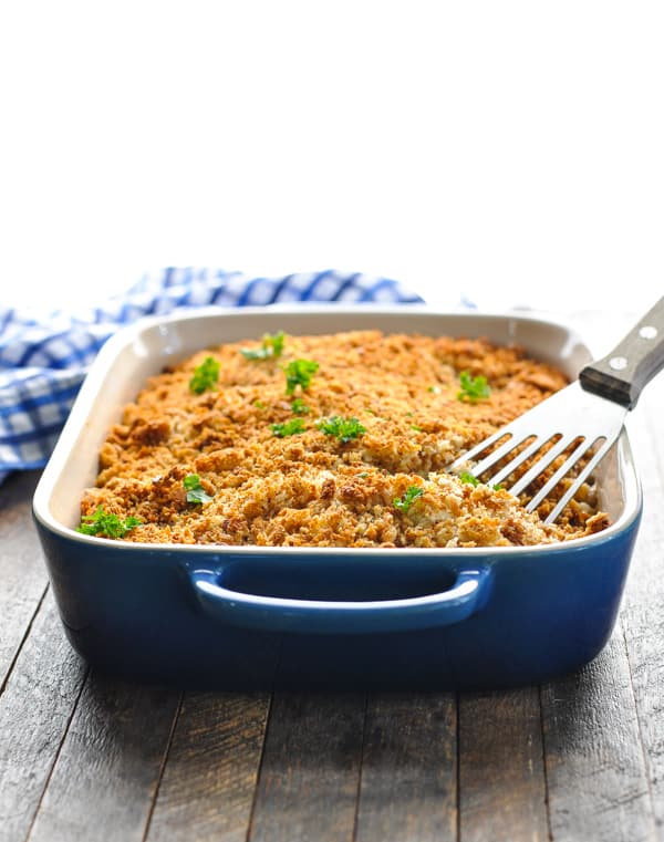 Baked Chicken Stuffing Casserole in blue dish with spatula for serving