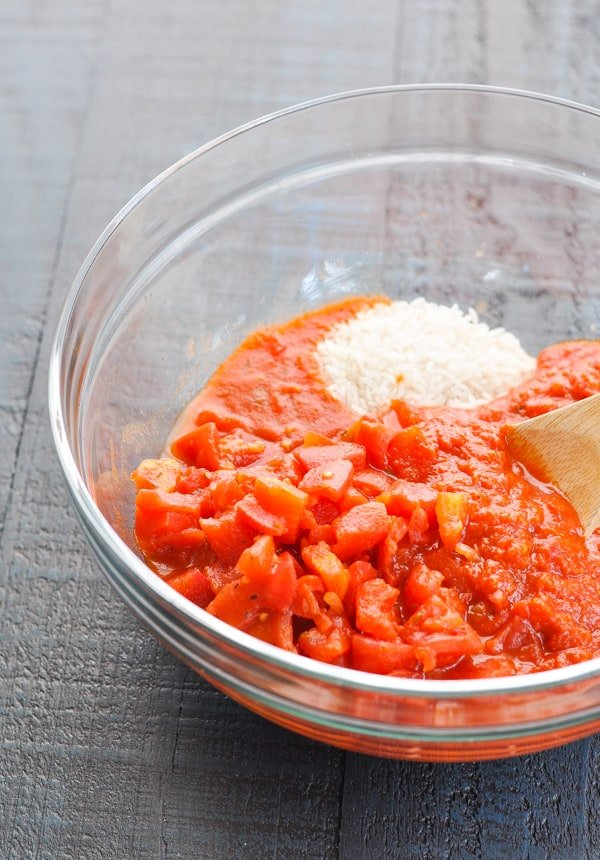 Rice, diced tomatoes and sauce in a glass mixing bowl